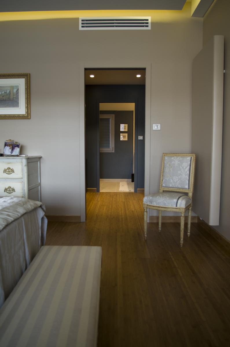 Vue en enfilade sur chambre, dressing et salle d'eau. Détail de la grille de climatisation : mise en œuvre sous flexible en plenum totalement invisible.